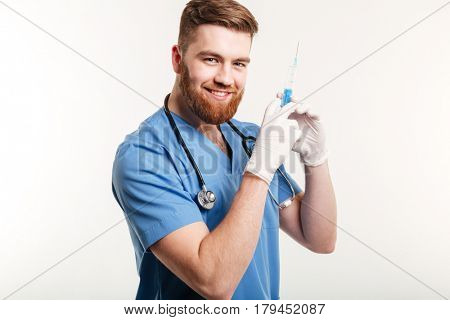 Portrait of a young attractive medical doctor or nurse holding syringe and looking at camera isolated on white background