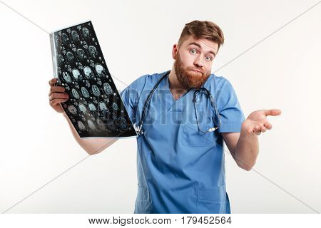 Portrait of a frustrated helpful medical doctor holding CT scan and looking at camera isolated on white background