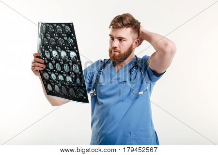 Portrait of a young medical doctor analyzing CT scan isolated on white background