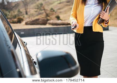 Closeup of businesswoman in yellow jacket closing the door of her car
