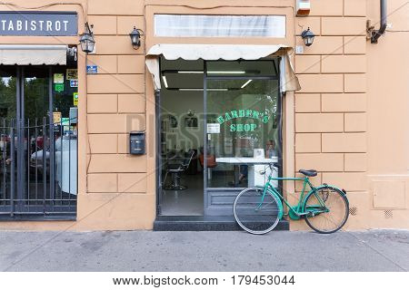 Florence ITALY- September 10 2016: Shop-window of barber shop with the barber (hairdresser) inside and bicycle parked near shop