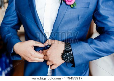 The groom fastens the button on his jacket