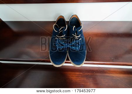 Groom's blue suede shoes and a blue dotted bow tie on the stairs