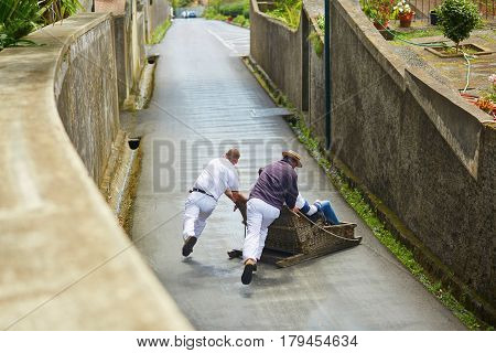 Toboggan Riders Pushing Wooden Sledge Downhill In Funchal, Madeira Island, Portugal