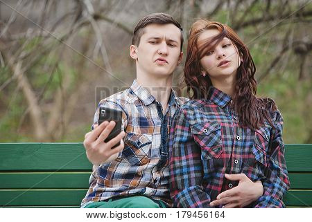 Young cheerful couple making selfie on a bench on a background of branches