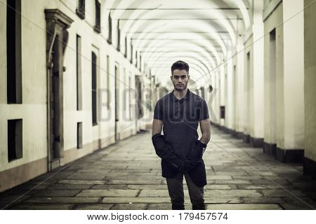 Handsome young man under cloisters in Italian city center, Turin, at night