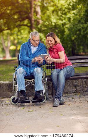 Disabled retiree man in park using tablet with smiling daughter