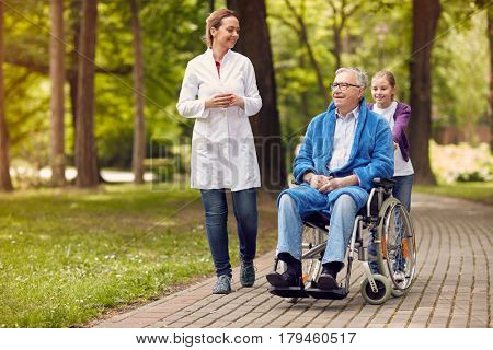 elderly man on wheelchair with caregiver nurse and granddaughter outdoor