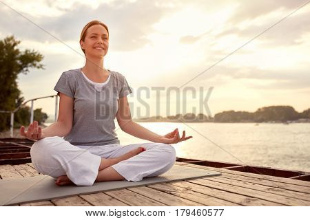 Pretty woman practicing yoga on dock by river
