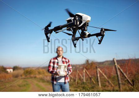 White modern drone hovering over vineyard