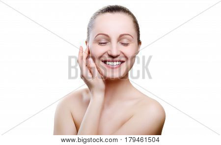 Portrait of a smiling girl with nude make-up with hands on chin isolated on white background. Girl with clean healthy skin on white. Cosmetology spa medicine beauty care.  Beautiful smile white teeth.