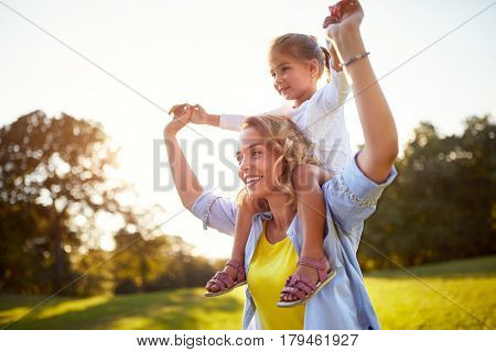 Young mother having fun with daughter outdoor