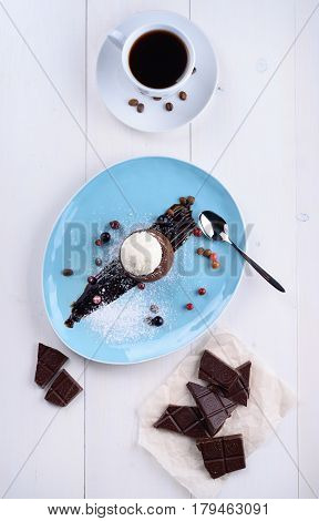 Chocolate fondant with ice cream pieces of chocolate and coffee on a white table
