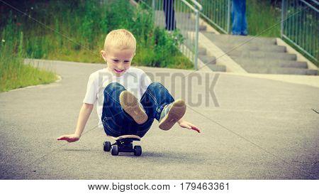 Child sitting on skateboard outdoor. Active boy skateboarding on pavement sidewalk. Kid practicing outside.