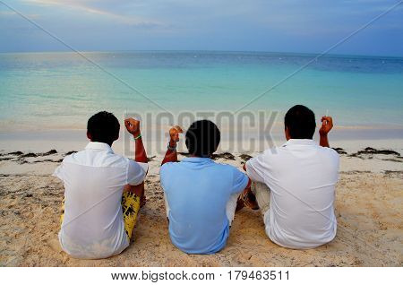 Three men face to ocean relaxing and smoking at the beach in Playa de Bavaro, Punta cana city, Dominican Republic. View of man's back.