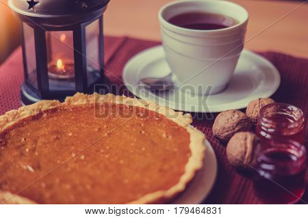 Cozy composition: pumpkin tart, black tea, cherry and strawberry jams and christmas candlestick