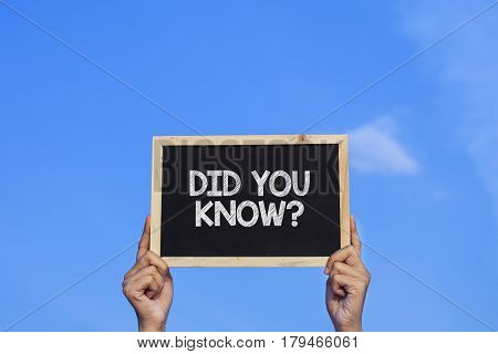 DID YOU KNOW? / Man holding small blackboard on blue sky background