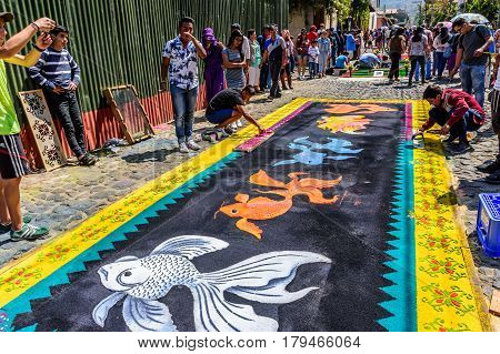 Antigua, Guatemala - March 26 2017: Locals make dyed sawdust procession carpets during Lent in colonial town with most famous Holy Week celebrations in Latin America.