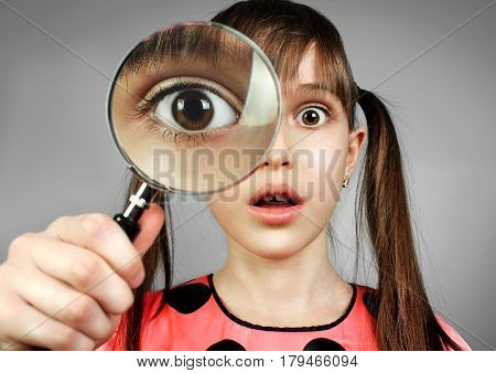 surprised girl searching with magnifying glass .