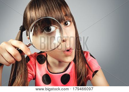 amazed child girl looking through magnifying glass searching concept