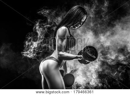 Muscular unrecognizable brunette in bikini doing exercise on biceps with dumbbells in smoke