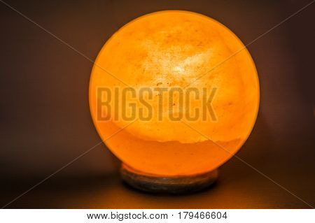 The lamp placed inside of the salt stone. Horizontal indoors shot of Himalayan salt round or spheric lamp