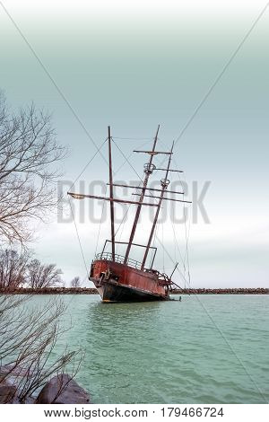 Rusty shipwreck with tall masts in a cover near shore dark stormy sky above