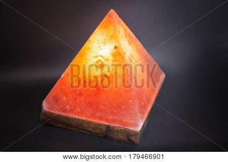 Lamp placed inside of salt stone. Horizontal indoors shot of Himalayan salt pyramid shaped lamp