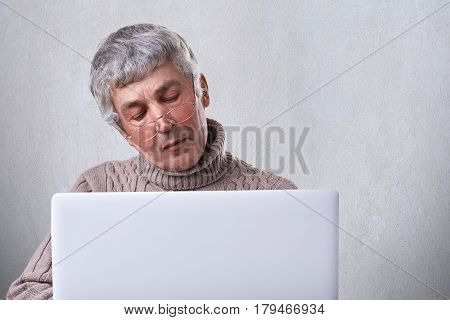 Surfing the net at home. Pensive mature man wearing eyeglasses and casual sweater reading a book on his laptop while siting at home having dreaming expression. People age leisure concept.