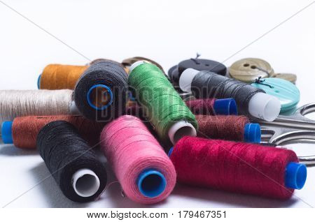 Colored spools of thread, buttons and scissors are a bunch on white background