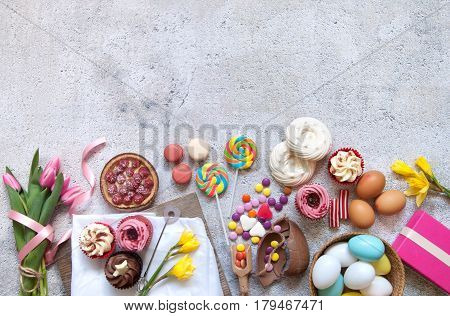 Selection of easter sweets bakery cupcakes chocolate eggs and confectionery with copy space