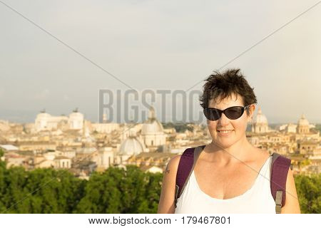 A middle aged female tourist poses in front of a view overlooking the capital of Italy, Rome.