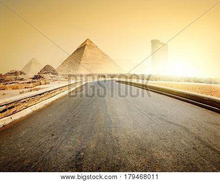 Asphalted road to piramids and modern buildings of Giza