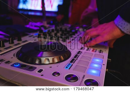 DJ mixer in bright colors disco in a nightclub. Audio equipment musician in a restaurant or cafe - a mixer for sound effects and music playback.