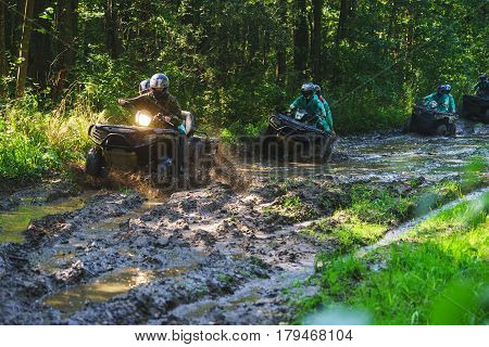 Summer Activities for adults - a trip on quad bikes on the road. Man on ATV in the mud on the road to participate in the race over rough terrain in the forest on a hot summer day.