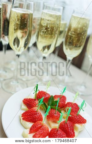 Strawberry fruit as a snack at the event. Snacks on a buffet table - fresh strawberries on pineapple. Catering snack during the event Champagne in glasses with a fruit snack.