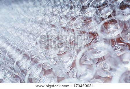 Clean glasses on a table prepared by the bartender for champagne and wine. Several of transparent glasses on a rack. Catering for the event preparation, clean glasses for drinks. Soft focus.