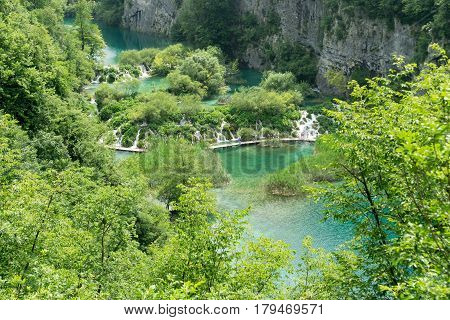 The view overlooking some of the waterfalls and lakes at Plitvice Lakes National Park with unrecognizable tourists walking along a pathway.
