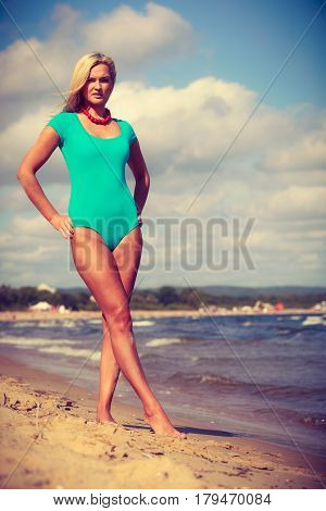Woman Walking On Beach Wearing Swimsuit