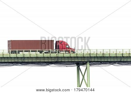 A red semi crosses a bridge in front of a white cloudy sky with plenty of copy space above and below