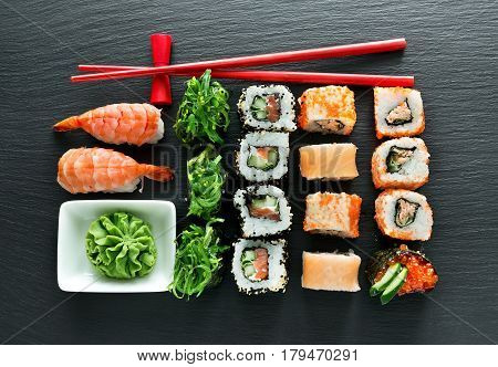 Set of sushi with wasabi and chopsticks on slate