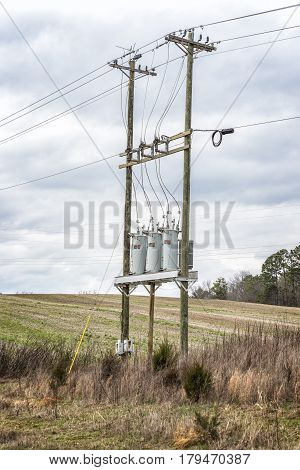 Vertical shot of Three Electric Utility Transformers On Telephone Poles under a cloudy sky.
