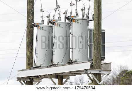 Horizontal shot of Three Electric Utility Transformers.