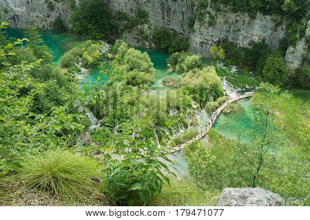 A high aerial view of many tourists crowding the walkways that cross the lakes and waterfalls at Plitvice Lakes National Park.