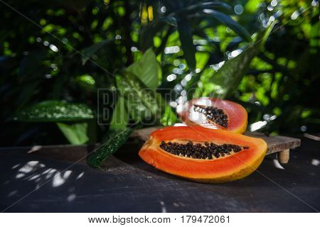 Still life of fresh and juicy tropical fruit on a dark shabby surface and green nature background. Vegan food: orange papaya with black seeds cut lengthwise into two halves. Healthy diet.