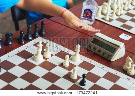 Child's hand during a game of rapid chess. Chess player clicks on the stopwatch button while playing a game of chess. Sports and hobbies - rapid chess.