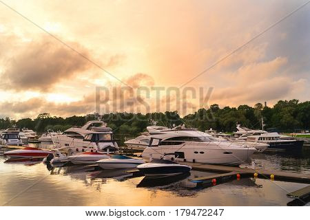 Luxury and high-speed costly yachts and boats at the docks moored to a pier on a summer evening. Vivid sunset on a summer evening on the quay with yachts and boats.