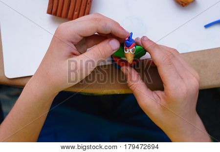 The child is engaged in modeling of plasticine sitting in the children's table with blanks and toys from plasticine. Educational and interesting activities for children. Rear view from above.