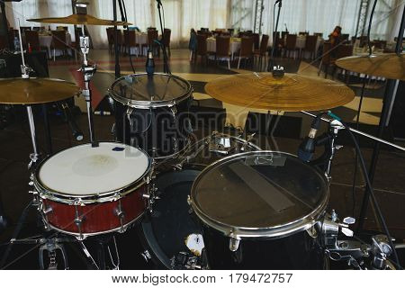 Drum kit on the stage in the main hall of the restaurant. Preparations for the event with a performance of musicians.