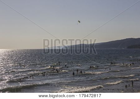 People who are swimming in the sea and paraglider at the background
